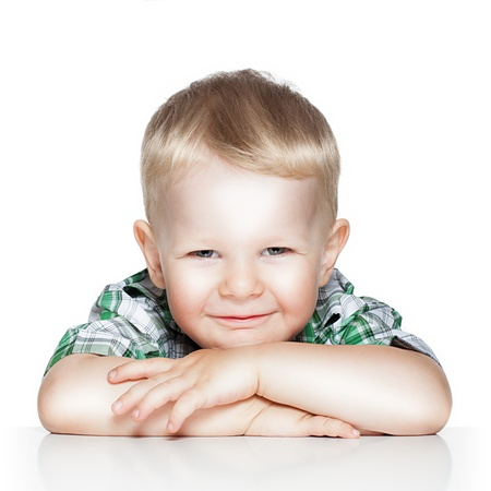 sitting small: Portrait of a cute little boy smiling while sitting at table, isolated over white