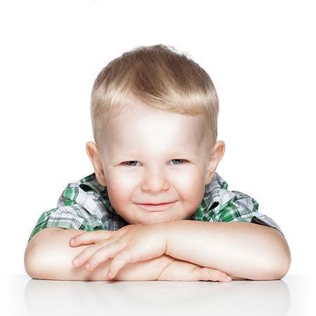 Portret van een leuke kleine jongen lachend zittend aan tafel, geïsoleerd over white Stockfoto
