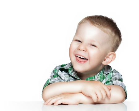 Portrait of a cute little boy smiling while sitting at table, isolated over white photo