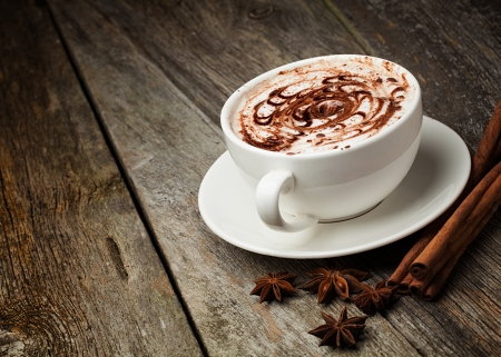 cappuccino: coffee cup and beans, cinnamon sticks, nuts and chocolate on wooden table on brown background