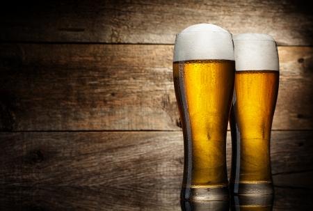 vasos de cerveza: Dos vasos de cerveza en el fondo de madera con copyspace Foto de archivo