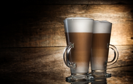 Fragrant coffee latte in glass cups and cinnamon on wooden table on brown background