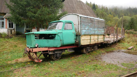 A homemade train with carriages, constructed from a car and a train, stands on the rails, waiting for a ride