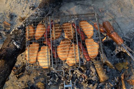 woodfire: White bread and sausages grilled over an open fire, grill Stock Photo