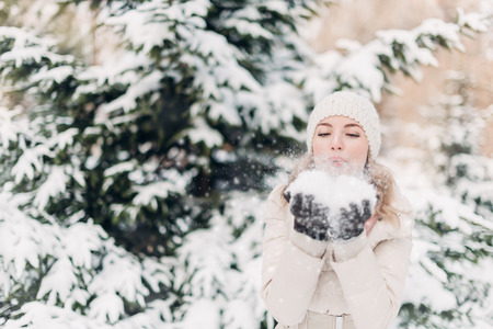 hands off: Beautiful woman in winter hat blows off snow from hands