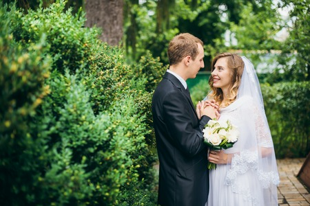 romantic flowers: Elegant bride and groom posing together outdoors on a wedding day Stock Photo