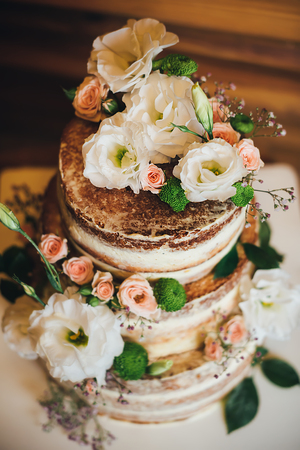 Wedding cake with roses whipped cream on a wooden background