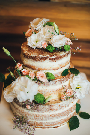 Wedding cake with roses whipped cream on a wooden background Reklamní fotografie