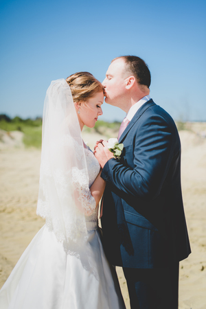 wife and husband: gorgeous stylish happy blonde bride and  elegant groom on a sand