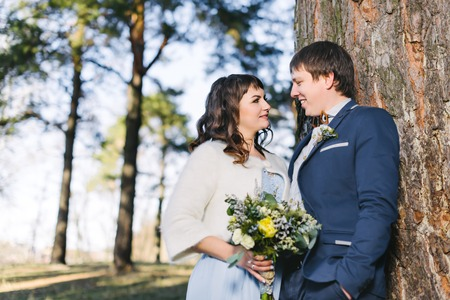 husband: Married Couple in forest embracing. Happy bride and groom. Wedding Stock Photo