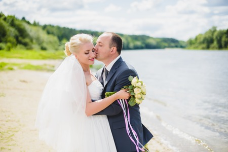 relationship love: Bride and groom walking on the river, smiling and kissing Stock Photo