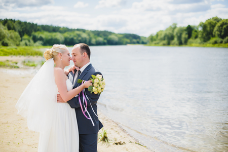romantic man: Bride and groom walking on the river, smiling and kissing Stock Photo