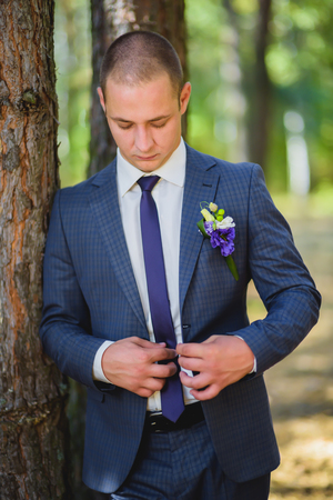fastens: fastens groom blue jacket in the park Stock Photo