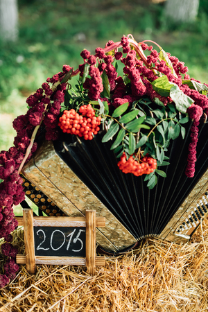 countrified: Accordion straw decorated with flowers and rowan