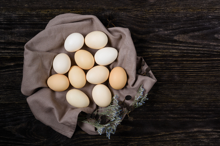 Chicken eggs in a nest of towels on a wooden background