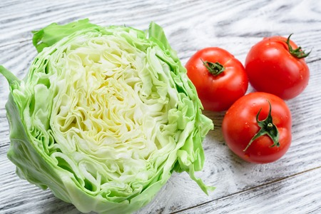 agriculturalist: Cabbage and tomatoes on a wooden background