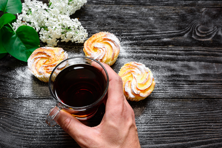 wenge: Black tea in a glass cup with cupcakes