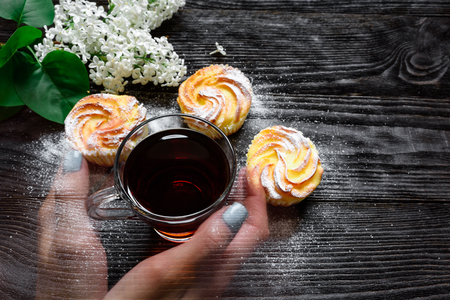 vitreous: Black tea in a glass cup with cupcakes