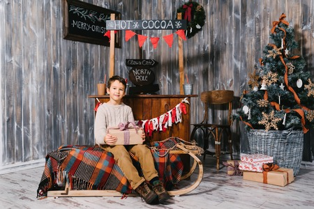 unwrapping: A child sitting on a sledge near a Christmas tree with Christmas gift