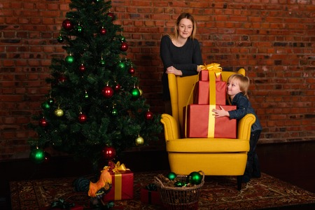unwrapping: Mom gives a child a Christmas gift near the Christmas tree