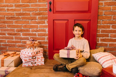 metis: Little boy opening gift for christmas, birthday
