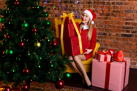 aciculum: A woman in a hat of Santa Claus sitting with a great gift near the Christmas tree