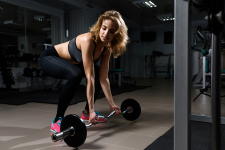 Beautiful young blonde girl in black clothes performing dead lift barbell exercises in gym