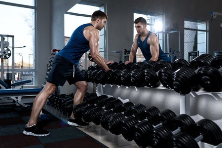 A sportive man in a T-shirt standing in front of a mirror takes dumbbells in the gym Stock Photo