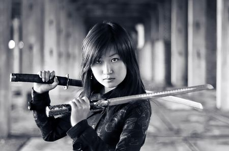 Dangerous asian girl with katana in ruins photo