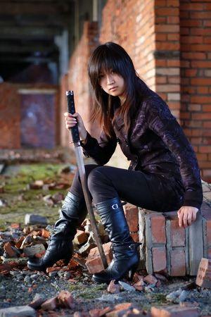 Dangerous asian girl with katana in ruins photo