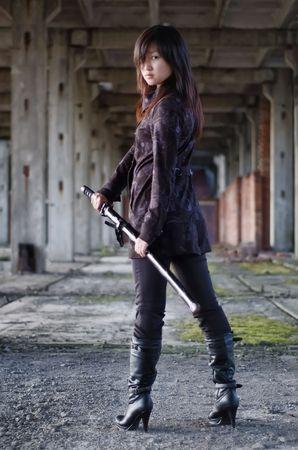 female assassin: Dangerous asian girl with katana in ruins Stock Photo