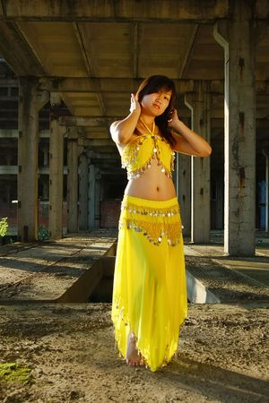 Pretty girl dancing in yellow indian dress photo