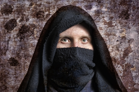 Spooky man in hood with rust wall on background Stock Photo - 6944880