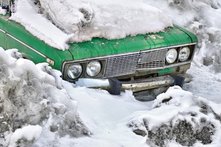 Old green car under snow in winter photo