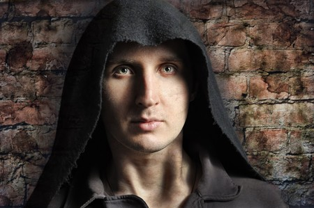 Spooky man in hood with brick wall on background photo