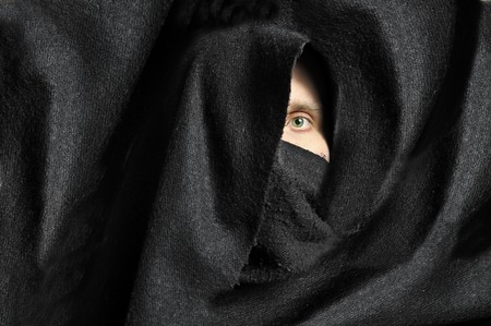 Male eye looking from black fabric Stock Photo - 7127095