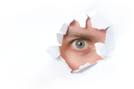 Eye looking through a hole in a paper Stock Photo - 7301659