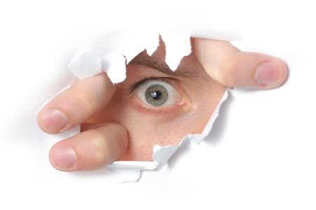 Eye looking through a hole in a paper Stock Photo - 7542096