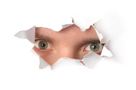 Eyes looking through a hole in a paper Stock Photo - 7591122