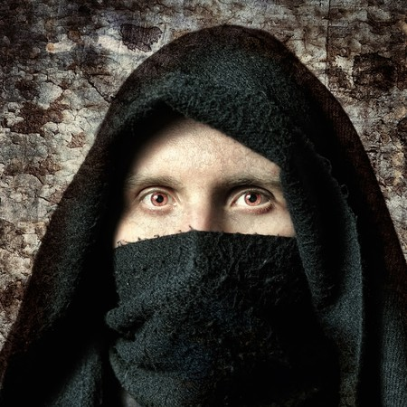 terrible: Spooky man in hood with terrible eyes
