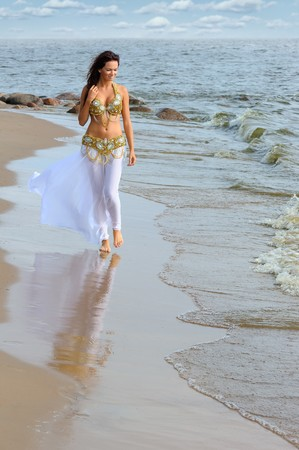 Beautiful young girl walking on the beach photo