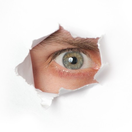 Eye looking through a hole in a paper Stock Photo - 7782290