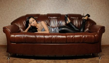 Woman relax on dark sofa photo