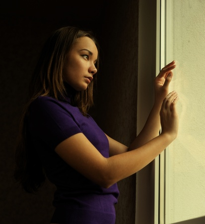 Young woman gazing out a window photo