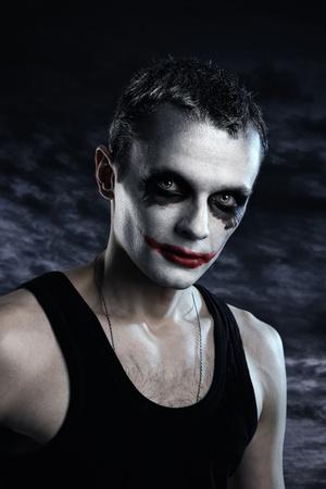 Spooky man joker on dark background photo