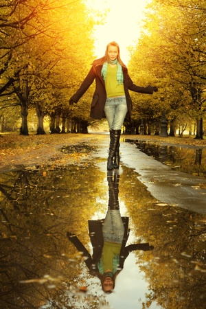 fall fun: Woman at autumn walking on puddle