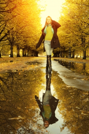 rainy season: Woman at autumn walking on puddle
