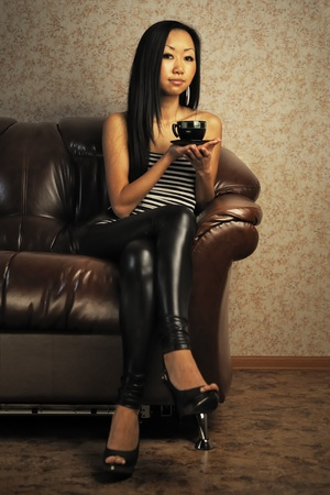 Woman with cup of tea sitting on sofa photo
