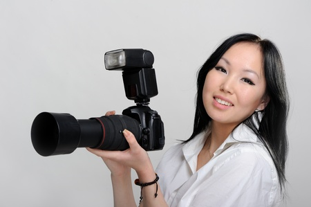 Asian woman with photo camera on white background photo