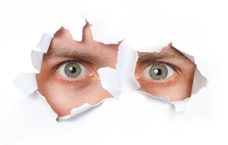 close up eye: Occhi guardando attraverso un buco in un documento isolato